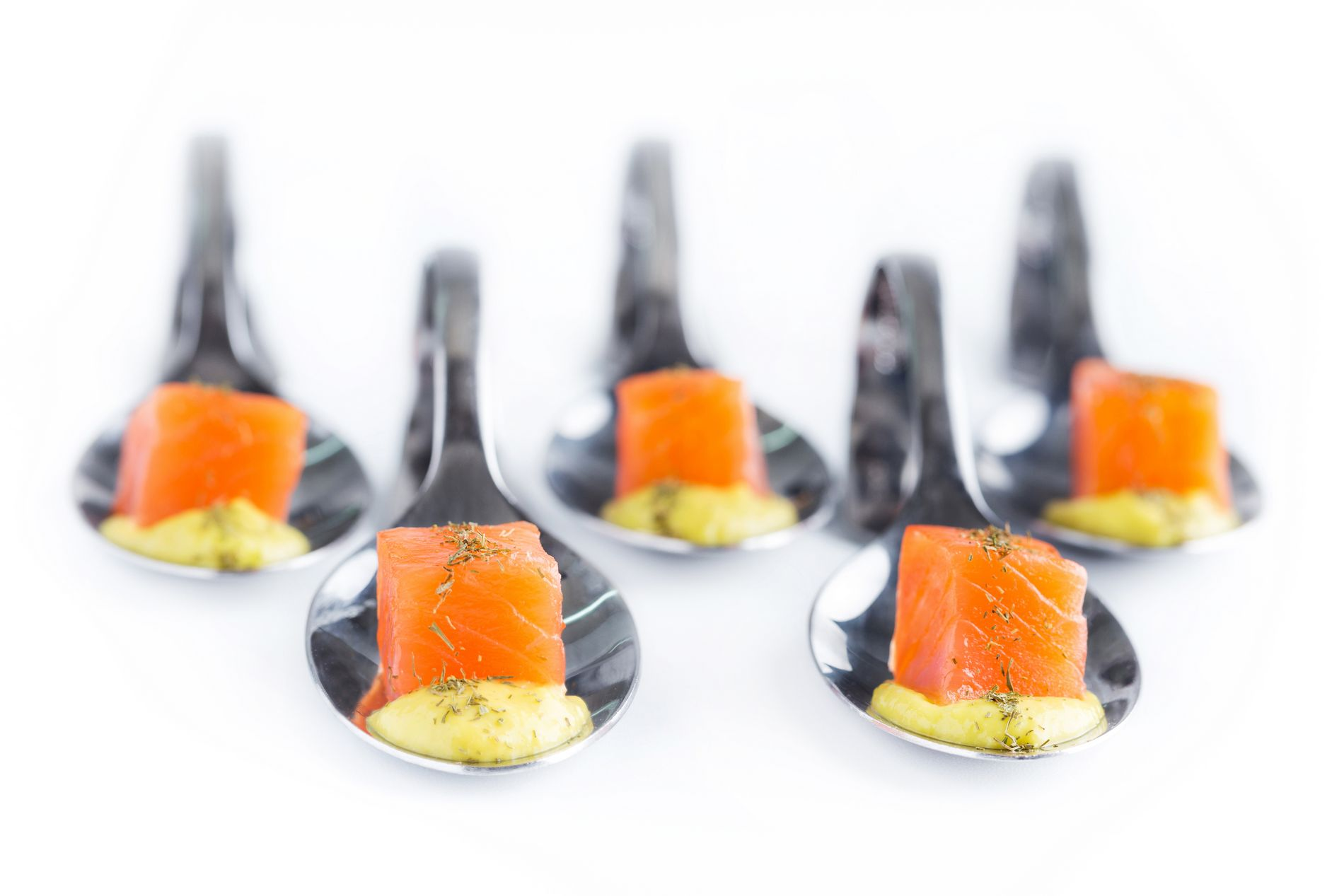 Cucharita con pastel de salmón sobre crema de aguacate y mango
